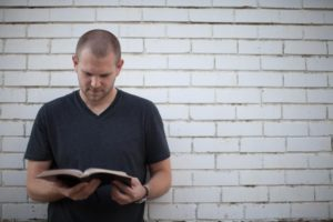 man-reading-bible-white-brick-wall